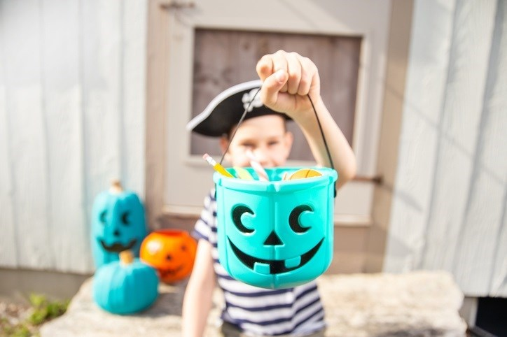 Young boy with a full teal pumpkin.