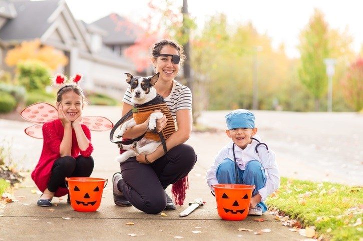 Family and dog trick or treating together.