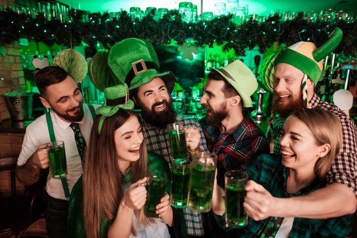 Friends celebrating St. Patrick's day together.  Silly green hats, green beer and smiling faces all around!